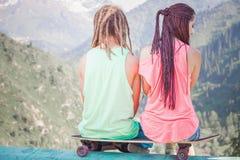 Les couples des jeunes hippies et à la montagne avec le longboard font de la planche à roulettes Image stock