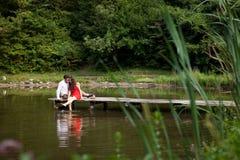 Les couples des personnes dans l'amour se reposent sur le pont Image stock