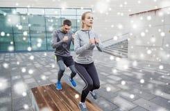 Les couples des sportifs faisant l'étape s'exercent sur le banc Photos libres de droits