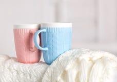Les couples des tasses avec la couleur de modèle, rose et bleue de tricotage sont sur la couverture tricotée par blanc chaud Photos stock