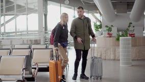 Les couples des touristes marchent au-dessus du hall de l'aéroport, portant des valises banque de vidéos