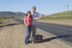 Les couples des touristes voyagent le monde faisant de l'auto-stop Photo stock