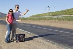 Les couples des touristes voyagent le monde faisant de l'auto-stop Images stock