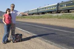Les couples des touristes voyagent le monde faisant de l'auto-stop Image stock
