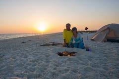 Les couples des voyageurs romantiques se reposent à côté du feu brûlant sur Photographie stock libre de droits