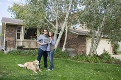 Les couples devant la nouvelle participation de maison ont vendu le signe de tableau noir Photos stock