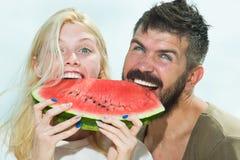 Les couples dr?les riant avec un blanc perfectionnent le sourire et se regarder dehors avec le fond unfocused Sourire image stock