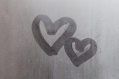 Les couples du résumé ont brouillé le symbole de coeur d'amour dessiné à la main sur le verre de fenêtre humide avec le fond de l Images stock