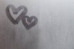 Les couples du résumé ont brouillé le symbole de coeur d'amour dessiné à la main sur le verre de fenêtre humide avec le fond de l Photos libres de droits