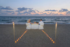 Les couples en mer échouent pendant le dîner romantique de luxe Photographie stock libre de droits