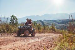 Les couples en vacances appréciant sur un vélo d'ATV montent Photo libre de droits