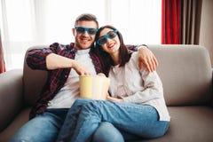 Les couples en verres 3D regardent la TV avec le maïs éclaté images libres de droits