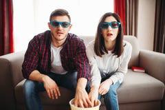 Les couples enchantés regardent la TV et mangent du maïs éclaté à la maison photo stock