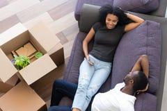 Les couples enthousiastes d'Afro-américain de vue supérieure faisant la pause, déballent des boîtes photos libres de droits