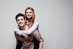 Les couples espiègles montant rire sur le dos ensemble pendant qu'ils jeune femme monte sur ses maris ferroutent, sur le fond gri Photo libre de droits