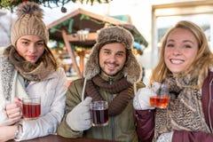 Les couples et l'ami boivent du vin chaud sur le marché de Noël Photo libre de droits