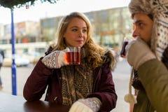 Les couples et l'ami boivent du vin chaud sur le marché de Noël Photos stock