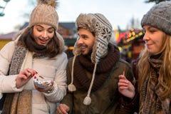 Les couples et l'ami boivent du vin chaud sur le marché de Noël Photos libres de droits