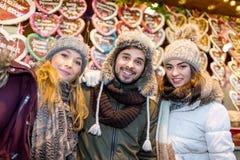Les couples et l'ami boivent du vin chaud sur le marché de Noël Photo stock
