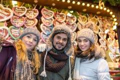 Les couples et l'ami boivent du vin chaud sur le marché de Noël Photographie stock libre de droits