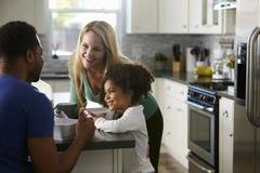 Les couples et la fille de métis parlent ensemble dans la cuisine Photos libres de droits