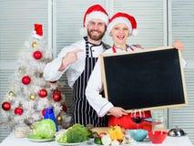 Les couples examinent des ingrédients de liste pour assurer le dîner de Noël Concept de recette de Noël Menu pour notre famille E photos stock
