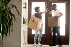 Les couples excités d'Afro-américain donnant haut cinq, célèbrent la relocalisation photographie stock libre de droits