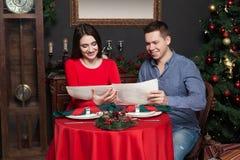 Les couples explorent le menu au restaurant de luxe Photographie stock