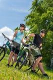 Les couples faisants du vélo de montagne de sport détendent dans les prés Photographie stock libre de droits