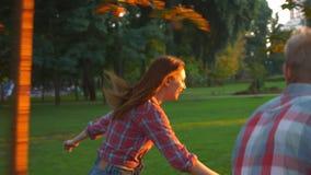 Les couples femelles et masculins, affectueux mignons sont courants, passants et tournants le cercle tout en accrochant en parc v clips vidéos