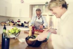 Les couples font cuire dans la cuisine ensemble image libre de droits