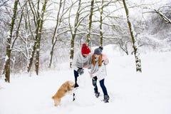 Les couples font le bonhomme de neige avec un chien dans la forêt d'hiver Photos libres de droits