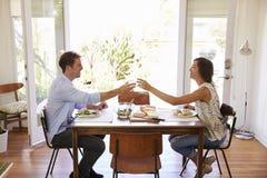 Les couples font un pain grillé pendant qu'ils apprécient le repas à la maison ensemble Photo stock