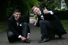 Les couples gais des mariés posent pour le whiel de photographies attachant des dentelles de chaussure Image stock