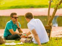Les couples gais se trouvant sur l'herbe à l'hiver sculptent la foire au Ni Photos stock