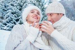 Les couples habillés confortables dans l'amour boivent chaud du thé dans la forêt d'hiver Image libre de droits