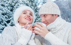 Les couples habillés confortables dans l'amour boivent chaud du thé dans la forêt d'hiver Photos stock