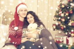 Les couples heureux célèbrent Noël à la maison Vacances d'hiver et concept d'amour Arbre et cadeaux de Noël Jaune modifié la tona Photos stock