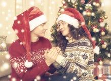 Les couples heureux célèbrent Noël à la maison Vacances d'hiver et concept d'amour arbre et décoration de Noël Jaune modifié la t Photos stock