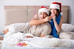 Les couples heureux célébrant des vacances de Noël dans le lit Photos stock