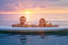 Les couples heureux détendent sur le panneau de palette au coucher du soleil Photographie stock