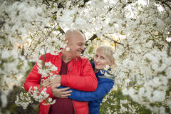 Les couples heureux d'aînés embrassent et sourient près de l'arbre de fleur ; Photographie stock libre de droits