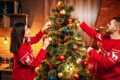 Les couples heureux d'amour décorent l'arbre de Noël Photo stock
