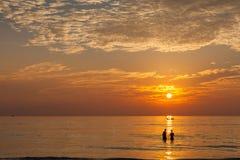 Les couples heureux dans l'amour apprécient le coucher du soleil de luxe Photographie stock libre de droits