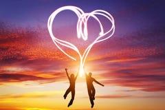 Les couples heureux dans l'amour sautent faisant le symbole de coeur de la lumière Image stock