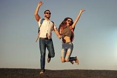 Les couples heureux dans l'amour sautent sur le ciel bleu, envie de voyager Images stock