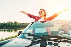 Les couples heureux dans l'amour vont en voiture de cabriolet dans le temps de coucher du soleil Images libres de droits