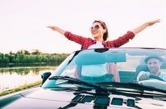 Les couples heureux dans l'amour vont en voiture de cabriolet dans le temps de coucher du soleil Image libre de droits