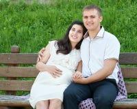 Les couples heureux dans la ville d'été garent la femme extérieure et enceinte, le jour ensoleillé lumineux et l'herbe verte, bea Images stock