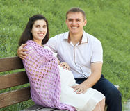 Les couples heureux dans la ville d'été garent la femme extérieure et enceinte, le jour ensoleillé lumineux et l'herbe verte, bea Photo stock